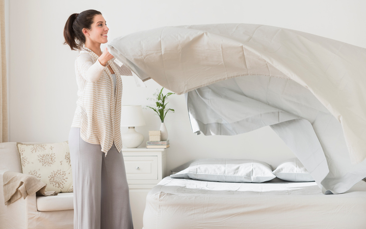 Woman spreading sheet on bed