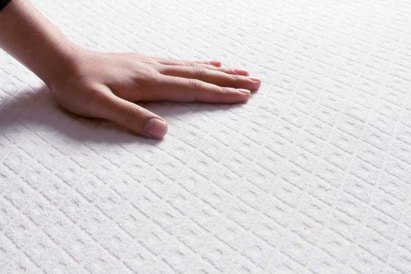 A hand on a white mattress